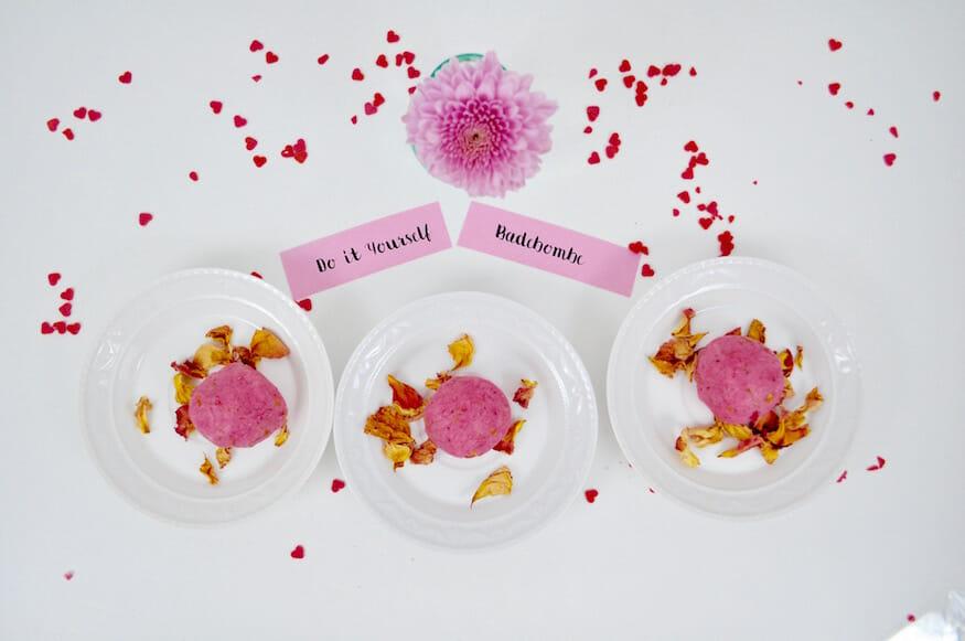 Drei fertige Badebomben mit Rosenblüten
